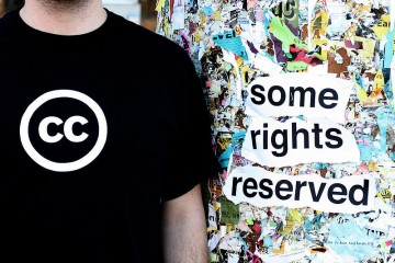 "Creative Commons T-shirt next to a graffiti wall stating ""some rights reserved"""